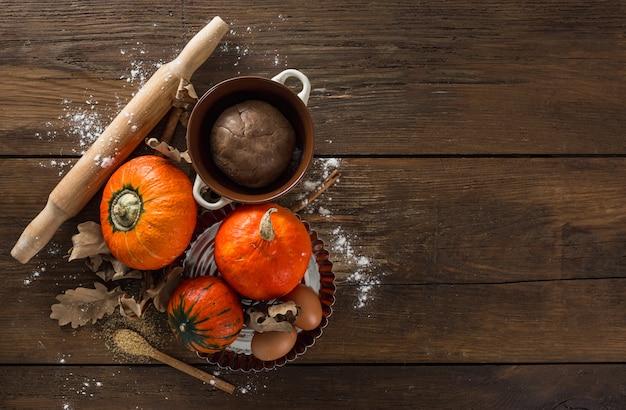 Masa cruda de pastel de calabaza con hojas secas de otoño, azúcar de caña, rodillo y canela