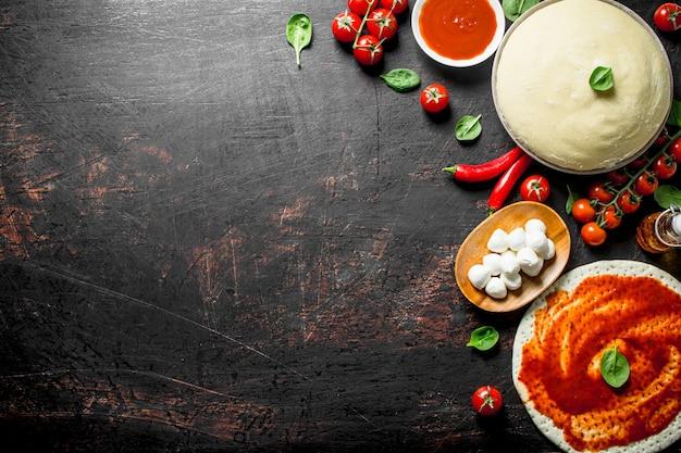 Masa con diferentes ingredientes para pizza casera. sobre fondo rústico oscuro