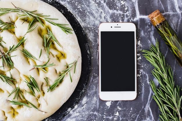 Masa de pan sin cocinar con romero y teléfono inteligente en la encimera de la cocina