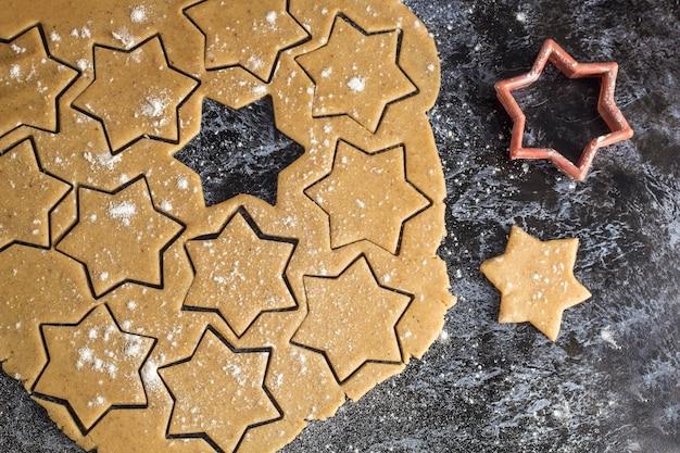 Masa de pan de jengibre casera cruda de navidad desplegada en la mesa oscura