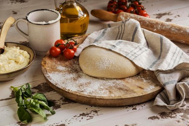 Masa de pizza cubierta con un paño junto a aceite y tomates