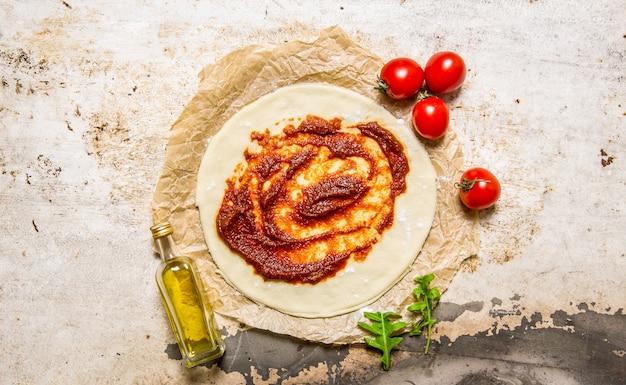 La masa de pizza extendida con pasta de tomate, aceite de oliva y tomates. sobre fondo rústico. vista superior