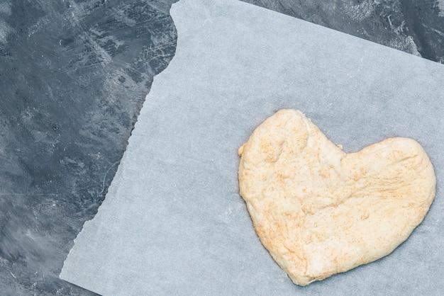 Masa de pizza hecha a mano en forma de corazón