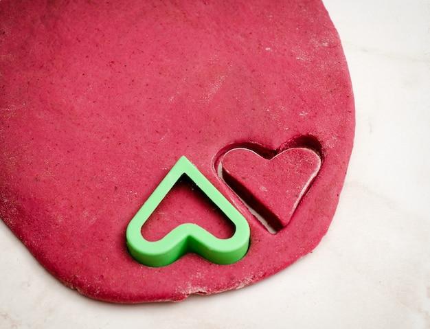 Masa de remolacha roja con un corazón cortado galletas, vista superior de cerca