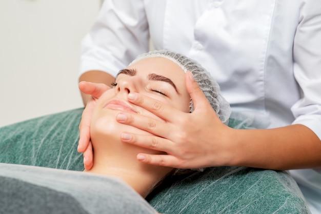 Masaje de cabeza de mujer joven por cosmetóloga en salón de belleza.