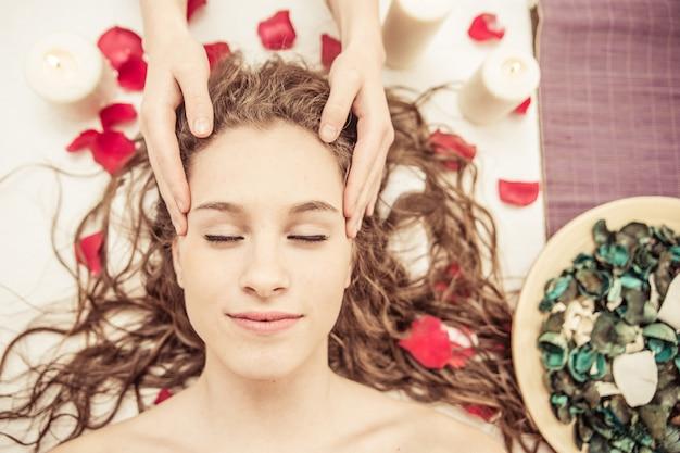 Masaje de cabeza. mujer joven haciendo masajes en el spa