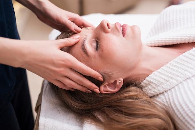 Masaje de cabeza a mujer relajada en el spa