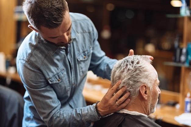 Masaje de cabeza. vista posterior del cliente senior de peluquería obteniendo su cabello peinado por un estilista profesional.