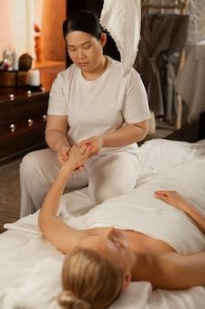 Masaje complejo. mujer asiática involucrada que trabaja como masajeadora experimentada y procesando el cuerpo de su cliente.