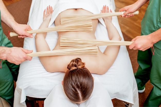 Masaje de espalda con escobas de bambú.