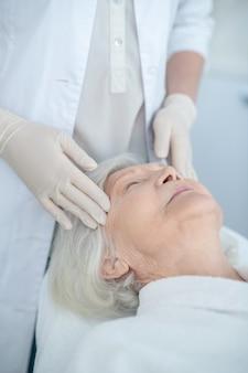 Masaje facial. mujer madura disfrutando de un masaje facial y aspecto relajado