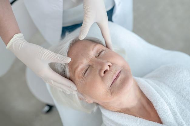 Masaje facial. mujer madura de pelo gris con un masaje facial y aspecto relajado