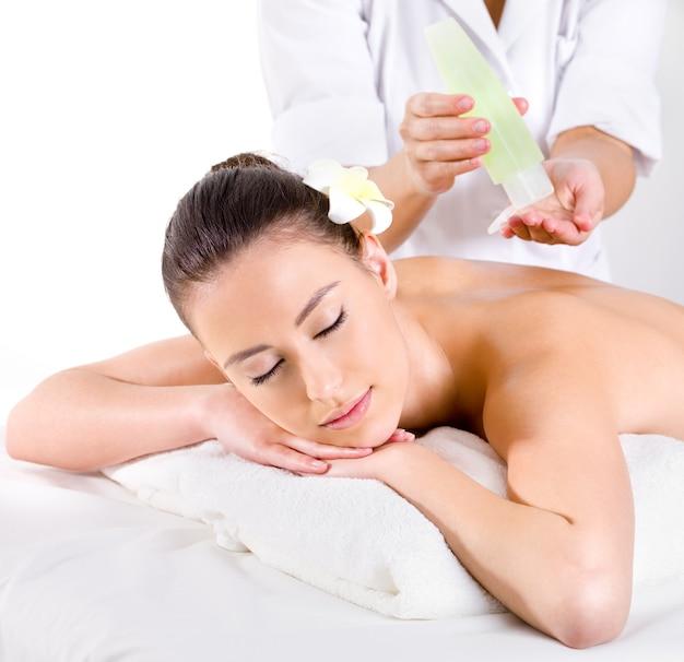 Masaje heathy para mujer joven con aceites aromáticos - horizontal - tratamiento de belleza