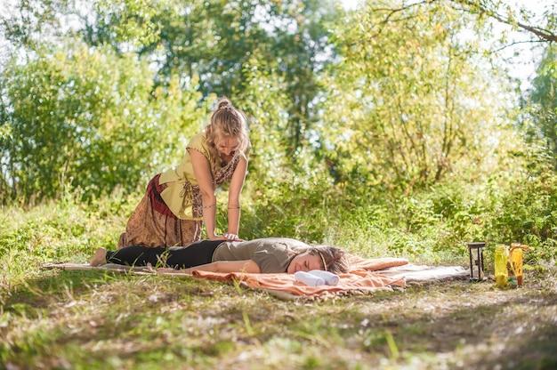 Masaje maestro realiza adecuadamente un gran masaje en el suelo del bosque.