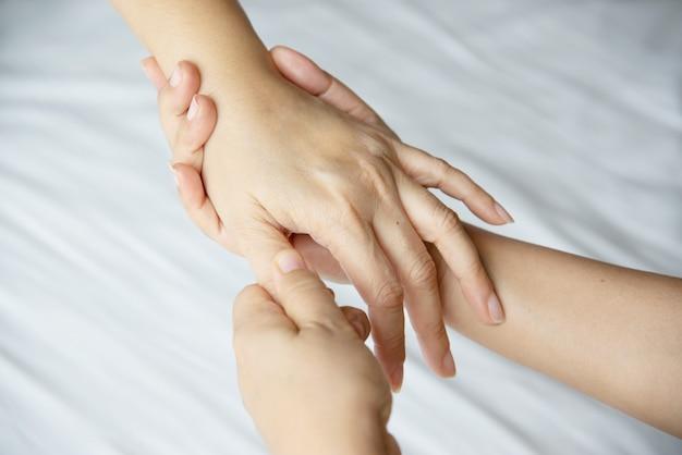 Masaje de manos sobre cama blanca limpia