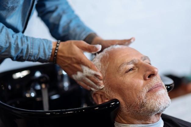 Masaje perfecto. retrato de primer plano de hombre barbudo agradable tener su cabello lavado por peluquero en peluquería.
