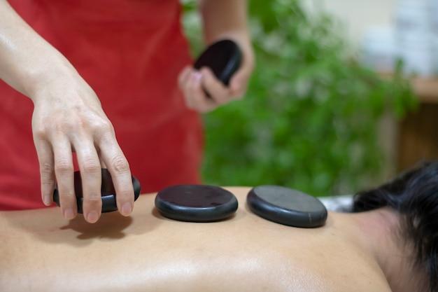 Masaje con piedras calientes en el salón de spa
