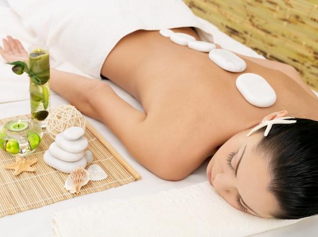 Masaje con piedras para mujer joven en el salón de belleza spa. terapia de recreación.