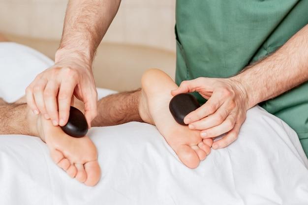 Masaje de pies con piedras calientes.