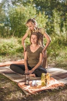 Masaje profesional realiza un relajante masaje sobre la hierba del bosque.