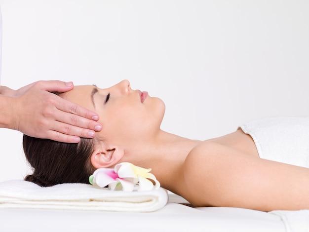 Masaje para el rostro de una mujer joven y bella - horizontal