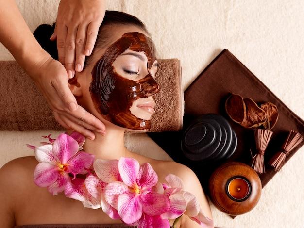 Masaje de spa para mujer joven con mascarilla facial en la cara - interior