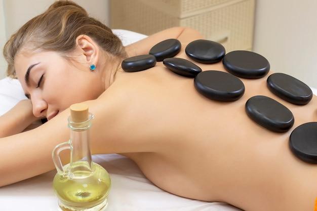 Masaje spa con piedras calientes. muchacha hermosa atractiva que miente en la cama del masaje en el salón del balneario. concepto de tratamientos de belleza y aromaterapia de spa