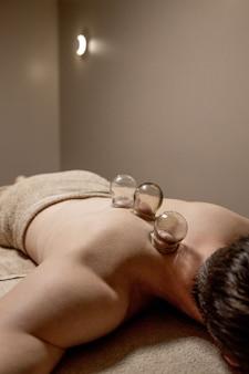 Masaje de ventosas joven disfrutando de masaje de espalda y hombros en spa