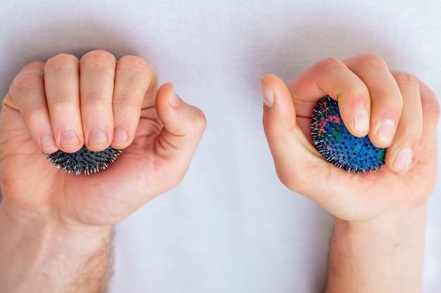 Masajea las bolas de goma en las manos.