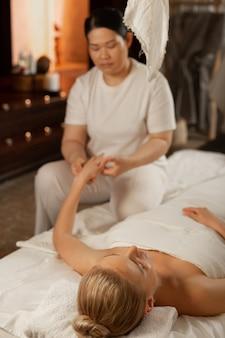 Masajeador experimentado. mujer guapa rubia con los ojos cerrados acostado en la cama cubierta y recibiendo masajes en las manos