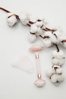 Masajeador gua sha y rodillo de jade sobre fondo blanco con algodón. concepto de belleza y anti edad.
