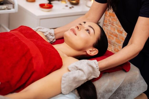 Masajeando cuidadosamente los hombros. señora agradable pacífica cubierta con una toalla roja disfrutando del procedimiento en el centro de spa profesional