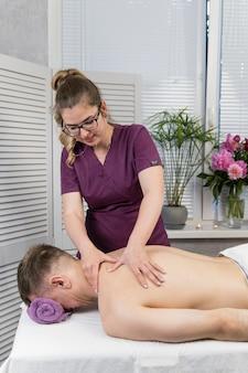 Masajista amasa los músculos de la espalda. hombre con masaje profesional en el salón de spa. masaje de bienestar de espalda y omóplatos.