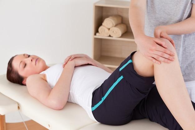 Masajista concentrando la rodilla de una linda mujer