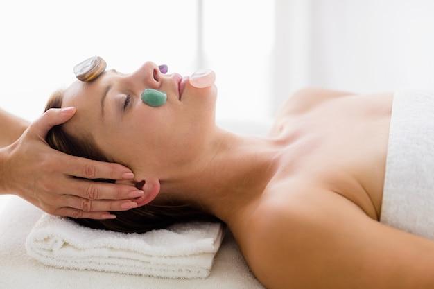 Masajista dando masaje facial con piedras a mujer