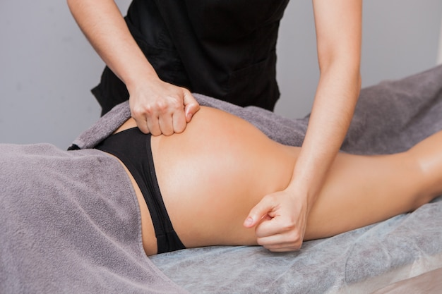 Masajista femenina hace masaje anticelulítico mujer joven cerca