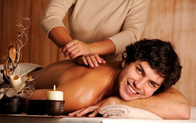 Masajista haciendo masaje a un apuesto joven feliz