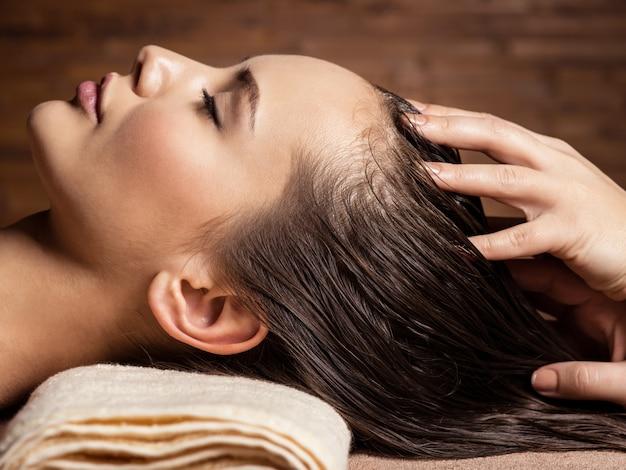 Masajista haciendo masaje en la cabeza y el cabello de una mujer en el salón de spa