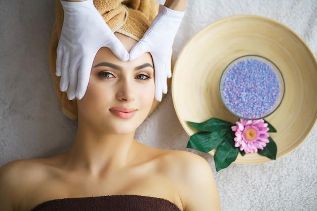 Masajista haciendo masaje la cabeza de una mujer en el salón de spa