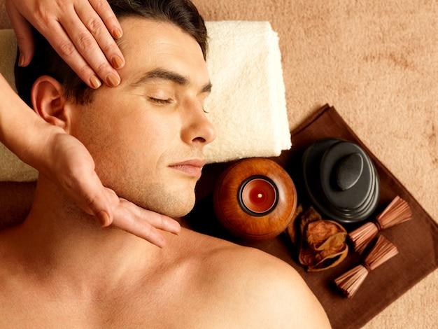Masajista haciendo masaje de cabeza de las sienes en el hombre en el salón de spa.