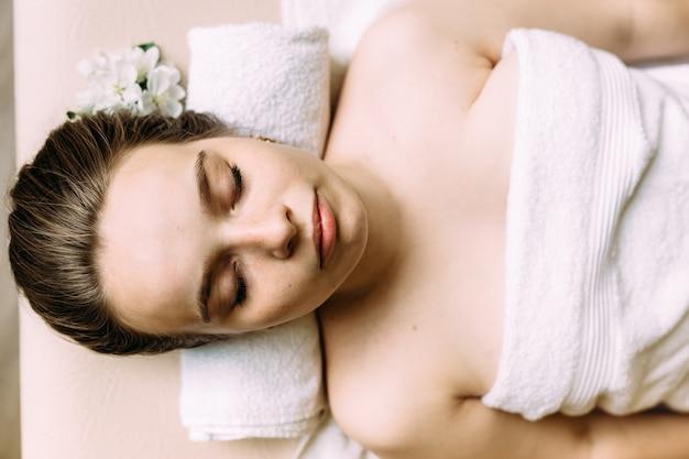 Masajista haciendo masaje en la cara de una mujer en el spa