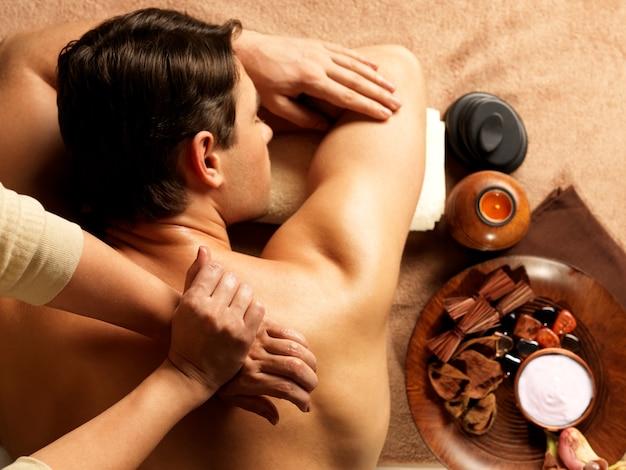 Masajista haciendo masaje de columna vertebral en el cuerpo del hombre en el salón de spa. concepto de tratamiento de belleza.