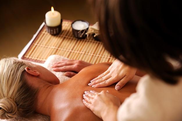Masajista haciendo masaje de la columna vertebral de la mujer en el salón de spa