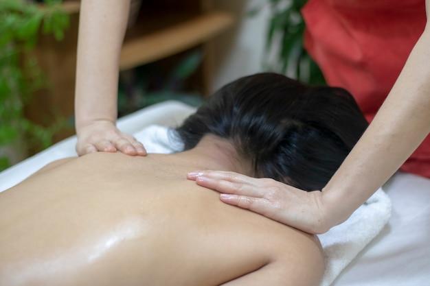 Masajista haciendo masaje en el cuerpo de la mujer en el salón de spa