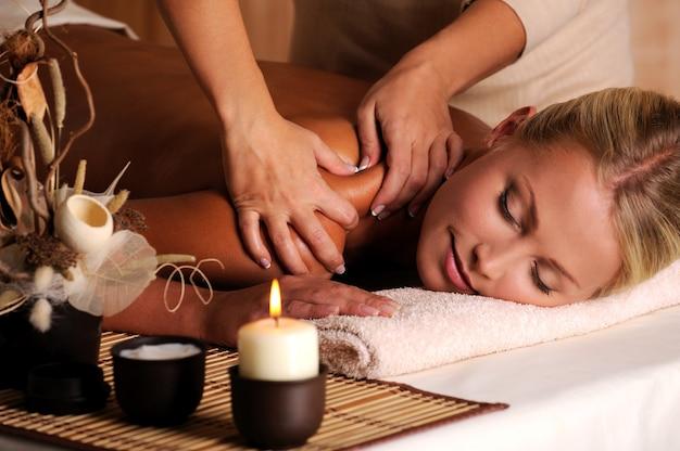 Masajista haciendo masaje en el hombro femenino en el salón de belleza Foto gratis