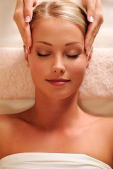 Masajista haciendo masaje en las sienes para joven hermosa mujer - vista de ángulo alto