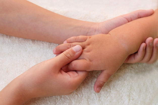 Masajista haciendo masajes dedos masita bebé.