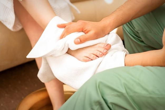 Masajista limpiando las piernas de la mujer después de un masaje de pies en el salón de spa