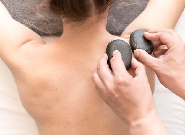 Masajista poniendo piedras en la espalda del cliente