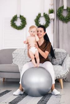 Una masajista profesional femenina con bebé feliz haciendo ejercicios con pelota de fitness en la sala médica. concepto sanitario y médico.